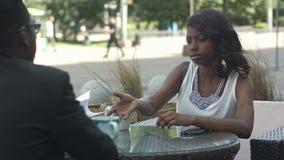 Afroamerikanergeschäftsmann, der die Papiere, Details eines Handels seinem schönen Partner erklärend beim Haben von a hält