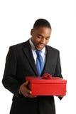 AfroamerikanerGeschäftsmann, der ein Geschenk anhält Stockbilder