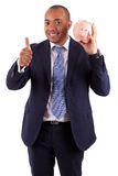 AfroamerikanerGeschäftsmann, der ein Sparschwein herstellt Daumen hält Lizenzfreie Stockfotos