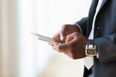 AfroamerikanerGeschäftsmann, der eine Tasttablette über Weiß verwendet Lizenzfreie Stockbilder