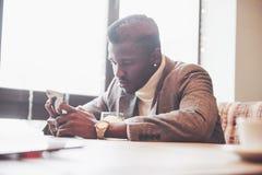 AfroamerikanerGeschäftsmann mit Laptop in einem Café Lizenzfreie Stockfotos
