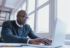 Afroamerikanergeschäftsmann, der an seinem Laptop arbeitet Stockfotografie