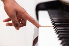 Afroamerikanerhand, die Klavier spielt Stockfotografie