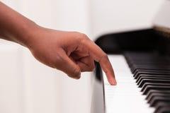Afroamerikanerhand, die Klavier spielt Stockbild