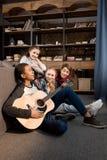 Afroamerikanerjunge, der acustic Gitarre spielt und während seine Freunde zu Hause hören singt Stockfotos