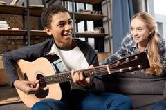 Afroamerikanerjunge, der acustic Gitarre während Mädchen zu Hause hört spielt Lizenzfreie Stockfotos