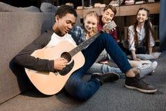 Afroamerikanerjunge, der acustic Gitarre während seine Freunde zu Hause hören spielt Stockfoto