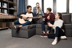 Afroamerikanerjunge, der acustic Gitarre während seine Freunde zu Hause hören spielt Stockbilder