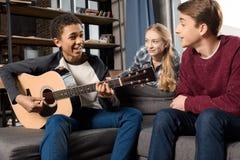 Afroamerikanerjunge, der acustic Gitarre während seine Freunde zu Hause hören spielt Lizenzfreie Stockfotos