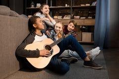 Afroamerikanerjunge, der acustic Gitarre während seine Freunde zu Hause hören spielt Stockfotos