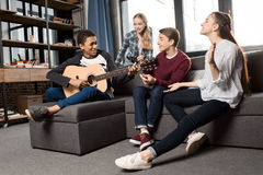 Afroamerikanerjunge, der acustic Gitarre während seine Freunde zu Hause hören und singen spielt Lizenzfreie Stockbilder