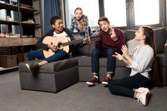 Afroamerikanerjunge, der acustic Gitarre während seine Freunde zu Hause hören und singen spielt Stockfoto