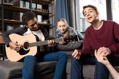 Afroamerikanerjunge, der acustic Gitarre während seine Freunde zu Hause hören und singen spielt Stockfotografie
