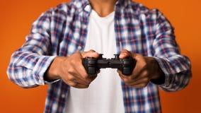 Afroamerikanerkerl, der online Videospiele, Steuerknüppel halten spielt stockfotografie