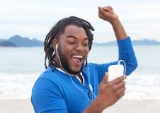 Afroamerikanerkerl mit Dreadlocks hörend Musik am Strand Stockbilder