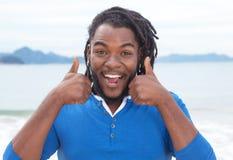Afroamerikanerkerl mit Dreadlocks hörend Musik am Strand Lizenzfreie Stockfotos