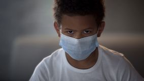Afroamerikanerkind in der medizinischen Maske, die in camera mit traurigen Augen, Epidemie schaut stockfoto