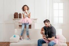 Afroamerikanermädchen, das während Vater zu Hause spielt Gitarre singt Stockfoto