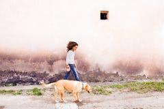 Afroamerikanermädchen mit ihrem Hund gegen Betonmauer Stockbild