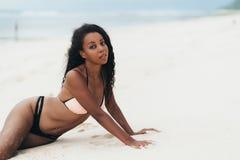 Afroamerikanerm?dchen in der Badebekleidung, die auf wei?em sandigem Strand liegt Sexy dunkelh?utiges Modell mit perfekten K?rper lizenzfreie stockfotografie