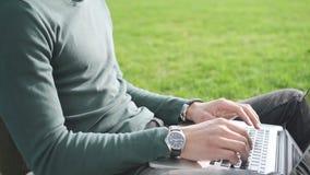 Afroamerikanermann, der an dem Projekt, draußen sitzend mit Computer arbeitet stock video