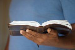 Afroamerikanermann, der die Bibel hält Stockfotografie