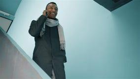 Afroamerikanermann, der die Treppe hinunter geht und am Telefon spricht stock video