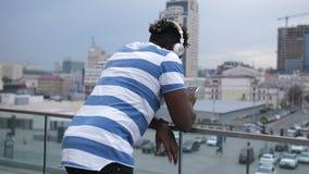 Afroamerikanermann, der draußen bewegliche APP überprüft stock video