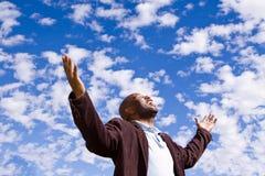 Afroamerikanermann, der draußen mit den offenen Armen stading ist Stockfotografie