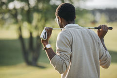 Afroamerikanermann, der Golfclub hält und weg schaut stockfotografie