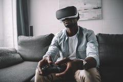 Afroamerikanermann, der Kopfhörer und Steuerknüppel der virtuellen Realität verwendet lizenzfreie stockfotos