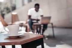 Afroamerikanermann, der an Laptop im lokalen Café arbeitet lizenzfreies stockfoto