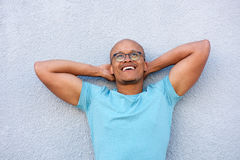 Afroamerikanermann, der mit den Gläsern oben schauen in der Betrachtung lächelt stockfoto