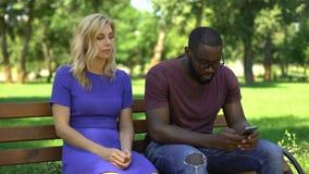 Afroamerikanermann, der Mobiltelefon auf Datum im Park, traurige Freundin ignorierend spielt stock video footage