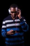 Afroamerikanermann, der Musik lokalisiert auf schwarzem backgr hört Stockfotografie