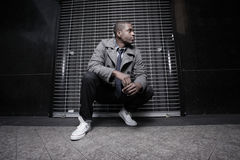 Afroamerikanermann, der nachts hockt Lizenzfreies Stockbild