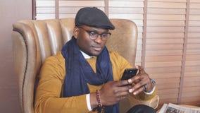 Afroamerikanermann, der schwarzen Hut, in einem Stuhl, rauchende Zigarre trägt stock video footage