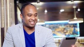 Afroamerikanermann, der seine Tablette in einem Café verwendet stock video