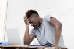 Afroamerikanermann, der zu Hause das Wohnzimmer arbeitet mit Laptop-Computer und Schreibarbeit sitzt lizenzfreie stockbilder