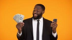Afroamerikanermann im Anzug-Holdingtelefon und in den Dollarscheinen, cashback stock footage