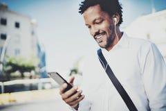 Afroamerikanermann in Kopfhörer standidng in der sonnigen Straße hörend auf Lieder am Handy, E-Mail unter Verwendung überprüfend Lizenzfreie Stockbilder