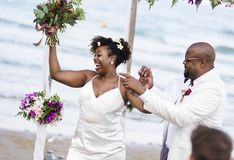 Afroamerikanerpaare, die am Strand heiraten lizenzfreie stockfotos