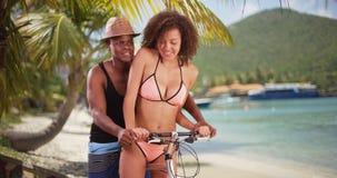 Afroamerikanerpaare reiten ihren Strandkreuzer entlang dem Ufer in den Karibischen Meeren Lizenzfreie Stockfotos