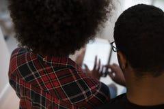 Afroamerikanerpaare unter Verwendung der Tablette zu Hause Stockbilder
