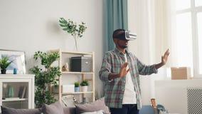 Afroamerikanerperson wird auf interessante Tätigkeit in den beweglichen Händen der Gläser der virtuellen Realität konzentriert, d stock video