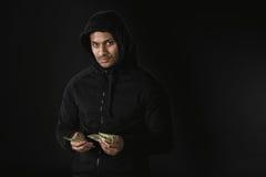 Afroamerikanerräuber im zoodie, das Geld lokalisiert auf Schwarzem hält Stockbild