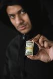 Afroamerikanerräuber im zoodie, das Geld lokalisiert auf Schwarzem hält Lizenzfreies Stockbild