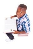 Afroamerikanerschuljunge, der ein Buch - schwarze Menschen liest Stockbild