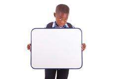 Afroamerikanerschuljunge, der ein leeres Brett - schwarze Menschen hält Stockfotos