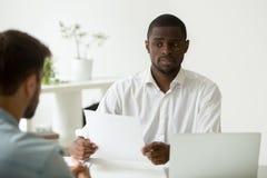 Afroamerikanerstunden-Manager, der zweifelhaftes skeptisches über hir schaut stockfotografie